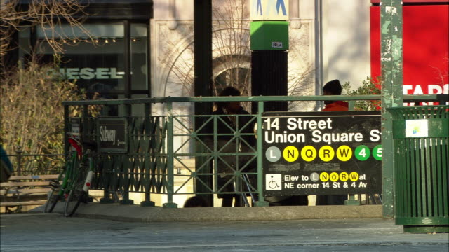 """medium angle of 14th street union square subway station. see pedestrians walk in, out, and around station.  see """"diesel"""" storefront. - union square new york city stock videos & royalty-free footage"""