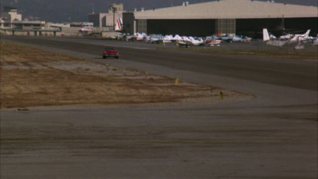 WIDE ANGLE OF A RED CONVERTIBLE, 1958 FORD THUNDERBIRD, DRIVING ON TARMAC OF AIRPORT WITH AIRPLANES, TERMINALS IN BG. CAR STOPS IN FRONT OF BODY OF SKYDIVER DEAD.  NEG CUT.  PRIVATE JETS CORPORATE JETS. CORPSE, DEAD BODY.