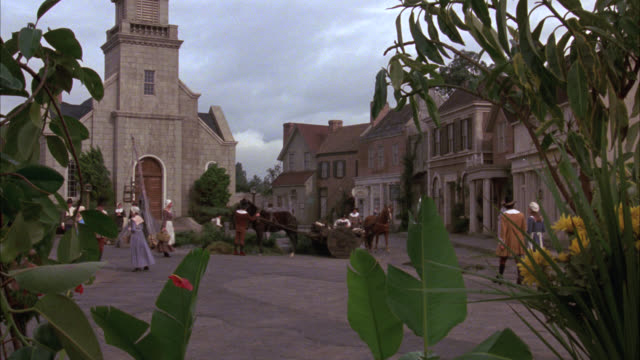 wide angle of people, towns folk, pilgrims walking through town square past stone church, storefronts. horse drawn wagon. small town. - hooved animal stock videos and b-roll footage