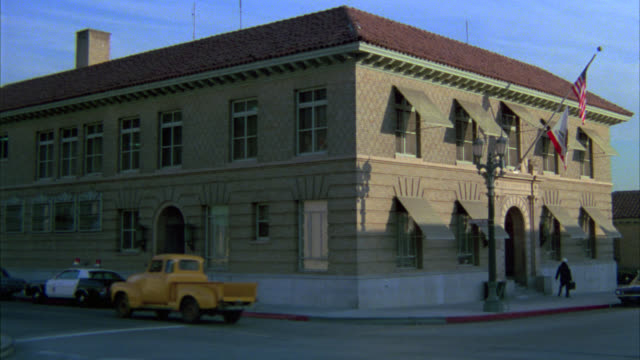 zoom in on police station div. 6 sign engraved in stone above entranec or door. old hollywood police station or precint on city street corner. - anno 1975 video stock e b–roll