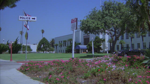 stockvideo's en b-roll-footage met wide angle of police department building. government office building. flowers in fg. palm trees. - politiestation
