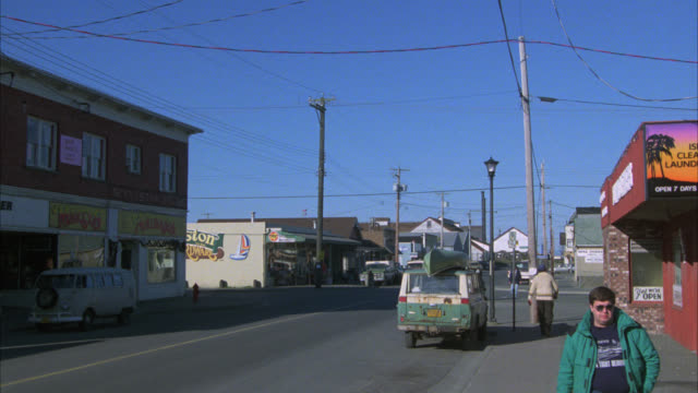 wide angle of cars driving on street and people walking on sidewalk in downtown area of small town. main street. one story and two story shops. - targa con nome della via video stock e b–roll