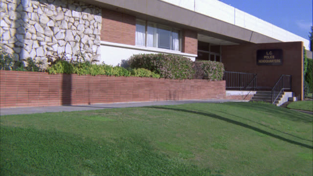 """ZOOM IN ON SIGN FOR """" L.C. POLICE HEADQUARTERS"""" ON BRICK BUILDING. POLICE STATION. COULD BE POLICE HEADQUARTERS FOR SUBURB, TOWN. GRASS LAWN."""