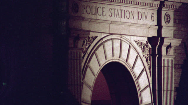 pull back from police station div. 6 sign engraved above entrance or door on building. cars on city street corner. old hollywood police station or precint. - police station stock videos & royalty-free footage