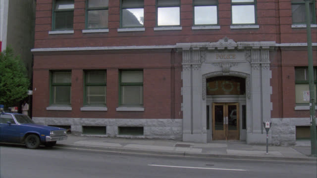WIDE ANGLE OF BRICK THREE OR FOUR STORY BUILDING. SIGN SAYS POLICE ABOVE DOOR OR ENTRANCE. CITY STREET IN FG. POLICE STATION, DEPARTMENT OR PRECINT.