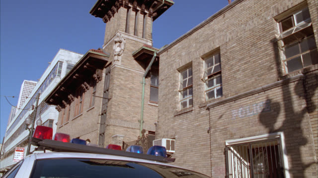 up angle of brick building, new orleans police department, precinct, or station. police cars parked on city street. - 警察署点の映像素材/bロール