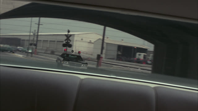 vidéos et rushes de medium angle driving pov straight back through rear window of black and white police car, lights flashing. driving through industrial area. warehouses. city streets. - 1974
