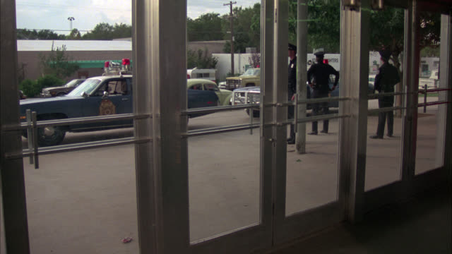 medium angle pov through front entrance, glass doors. police officers. could be police station or department. could be office building. - 1960 stock-videos und b-roll-filmmaterial