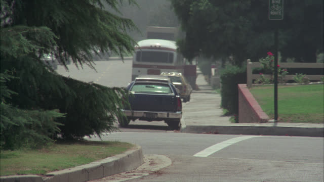 pan left to right of police car speeding, driving around corner on residential city street. could be emergency or car chase. - 1975年点の映像素材/bロール