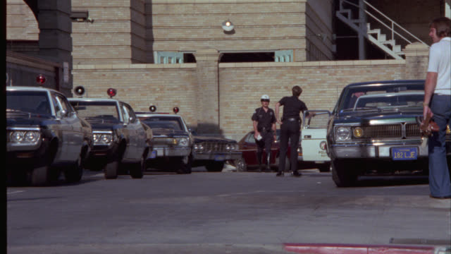 pull back from police car driving past two story brick building, police station, precinct or department. police station in hollywood. police officers and pedestrians walking. parked cars. government office building. - 1976 stock videos and b-roll footage