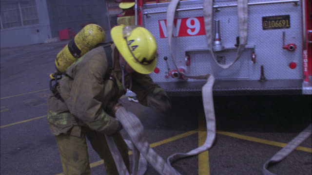 stockvideo's en b-roll-footage met medium angle of a firefighter carrying hose away from fire truck or fire engine. fire action. emergencies. - fire hose
