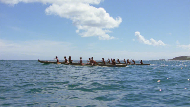 pan right to left from as native or indigenous hawaiian men row boats close to island. blue water. tropical. - indigenous culture stock videos & royalty-free footage