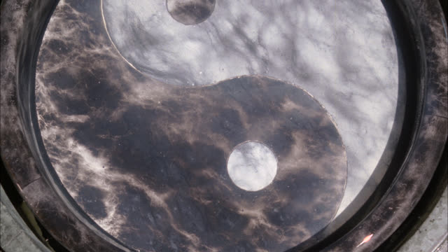 close angle of reflection bowl with ying-yang design on bottom. could be holy water. marble or stone. could be in temple. - holy water stock videos & royalty-free footage