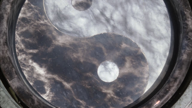 close angle of reflection bowl with ying-yang design on bottom. could be holy water. marble or stone. could be in temple. water ripples. - holy water stock videos & royalty-free footage