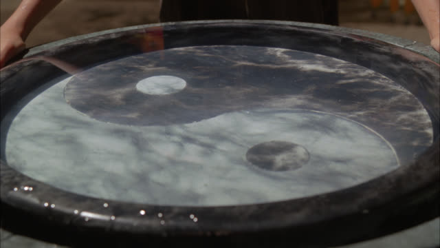 close angle of reflection bowl with ying-yang design on bottom. could be holy water. marble or stone. could be in temple. two hands hold sides of bowl. water ripples. - holy water stock videos & royalty-free footage