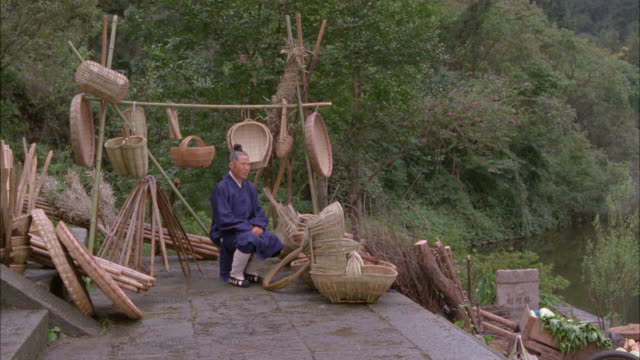 medium angle of elderly woman sitting on stool with straw baskets. trees, woods, or forest in bg. could be rural area. another woman with head of celery runs towards camera. could be rural marketplace. - korb stock-videos und b-roll-filmmaterial