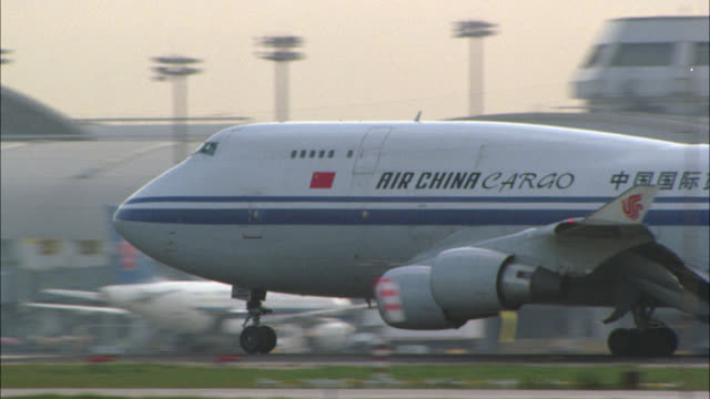 medium angle of air china cargo plane taking off from beijing capital international airport runway. terminals visible in bg. control towers. other planes visible. - peking stock-videos und b-roll-filmmaterial
