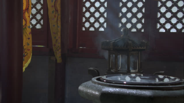 medium angle of reflection pool or holy water in stone bowl. smoke or incense in decorative lantern in bg. banners or decorative cloth hangings in bg. could be temple. - holy water stock videos & royalty-free footage