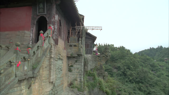 vídeos de stock e filmes b-roll de pan up of woman practicing martial arts on stone ledge on side of building with chinese pagoda roofs. could be temple or monastery. mountaintop. trees of forest below. stunt. taoist monastery in wudang mountains. - peitoril de janela