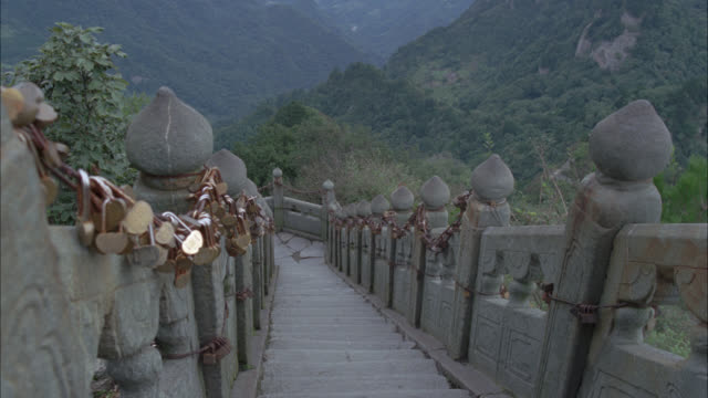 high angle down stone staircase. steps. chain covered in locks hanging on railings. mountains in bg. trees of forest. - chain stock videos & royalty-free footage