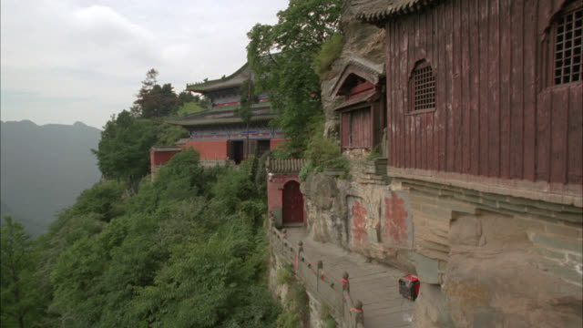 pan down of building with chinese pagoda roofs, built into side of cliff of mountain. could be temple or monastery. trees of forest below. taoist monastery in wudang mountains. - pagoda stock videos & royalty-free footage
