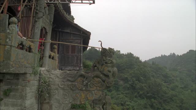 vídeos de stock e filmes b-roll de medium angle of snake on edge of stone ledge of building on mountaintop. trees, forest in bg. taoist monastery in wudang mountains. - peitoril de janela