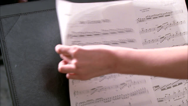 "close angle of book of sheet music with ""chopin's nocturnes"" written on cover. hand places sheet music on stand entitles ""we gonna win."" violin music. - music stand stock videos & royalty-free footage"