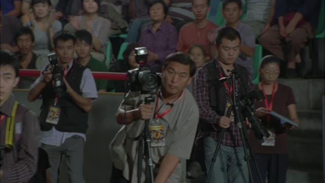medium angle of men or photographers at sporting event. cameras and equipment. crowd of people, spectators in stands in bg. could be in stadium or arena. - photographer stock videos & royalty-free footage