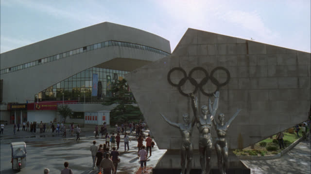 pan right to left from olympic rings and statue to crowds of people or spectators walking towards modern glass building, stadium, gymnasium or arena. sports. - olympic rings stock videos & royalty-free footage