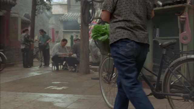 medium angle of courtyard or urban alley way. people sit on stools talking. others stand reading newspapers. bicycles visible. asian style architecture. - missing people stock videos & royalty-free footage