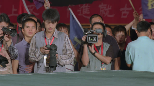 medium angle of crowds or spectators watching martial arts match. people cheer and clap holding flags and banners. chinese symbols or characters. - sequential series stock videos & royalty-free footage