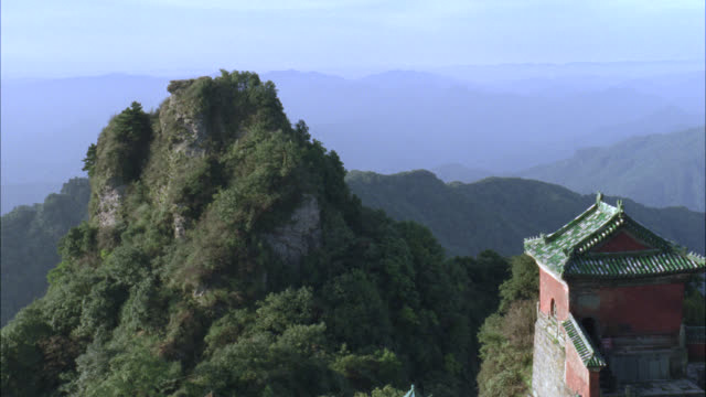 pan left to right from trees of forests on mountain to roof of temple, monastery, or pagoda. - treehouse stock videos & royalty-free footage