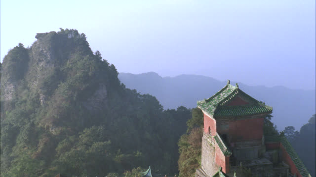 pan down to chinese temple, pagoda or monastery on edge of cliff. mountains covered with trees of forest or woods. fog. rooftops. - pagoda stock videos & royalty-free footage