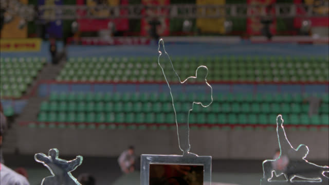 CLOSE ANGLE OF GLASS KARATE TROPHIES WITH CHINESE WRITING SITTING ON TABLE. ASIA. SPORTS ARENA OR STADIUM WITH EMPTY SEATS VISIBLE IN BG.