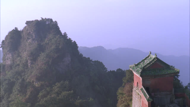 vidéos et rushes de pan left to right from trees of forests on mountain to roof of temple, monastery, or pagoda. - lieu de culte