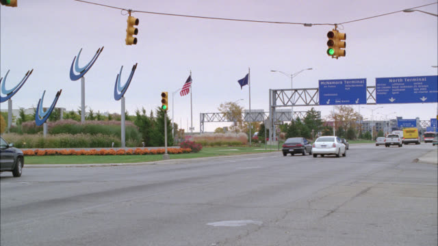 vídeos de stock, filmes e b-roll de wide angle of cars, taxis and shuttle buses driving on city streets, near detroit metropolitan airport. autumn leaves on trees in bg. overcast. signs for mcnamara and north terminals. - detroit michigan