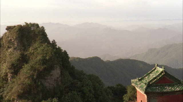 pan left to right from trees of forests on mountain to roof of temple, monastery, or pagoda. - pagoda stock videos & royalty-free footage
