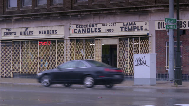 wide angle of lower class city street. discount candles sign and store. street signs for russell and gratiot. man shuts gate in front of shop. cars and taxi drive by. - michigan点の映像素材/bロール