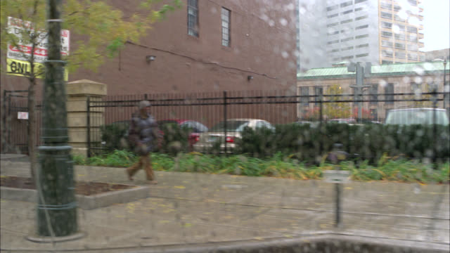 wide angle driving pov 3/4 right forward on city street. stores and shops. commercial area. rain. - michigan点の映像素材/bロール