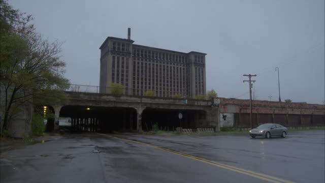 wide angle of taxi driving under rundown freeway or train overpass in lower class area. abandoned, high rise building, michigan central station, in bg. streets wet from rain. overcast. - ミシガン州点の映像素材/bロール