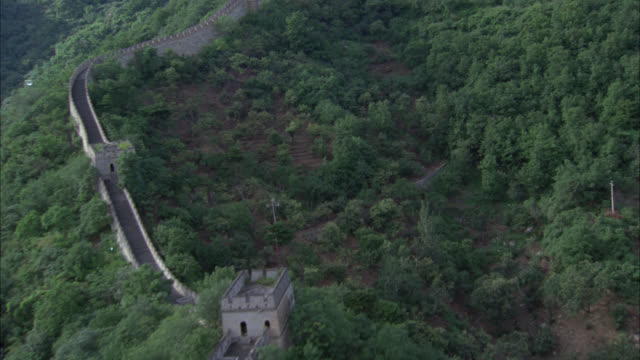stockvideo's en b-roll-footage met aerial of great wall of china across mountaintops covered in forests or trees. - chinese muur noord china