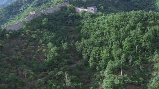 aerial of great wall of china across mountaintops covered in forests or trees. - chinesische mauer stock-videos und b-roll-filmmaterial