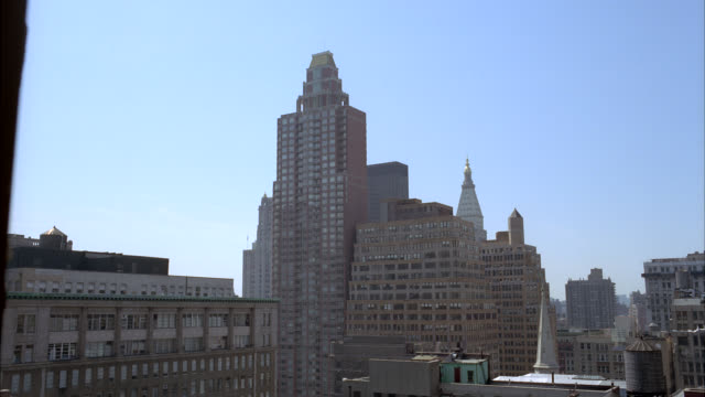 stockvideo's en b-roll-footage met wide angle of roofs or rooftops of city skyline. high rises and skyscrapers. could be apartment or office buildings. metlife tower in bg. windows. water tank or tower on roof of building in fg. church steeple visible. - metlife building