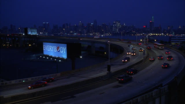 wide angle of cars driving on freeway or highway, near weehawken entrance to lincoln tunnel. charter buses. new york city skyline, midtown manhattan, in bg. billboards or advertisements. - bus billboard stock videos & royalty-free footage