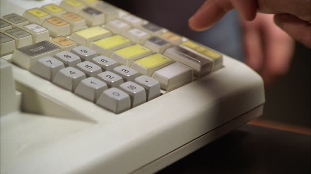 vídeos de stock e filmes b-roll de close angle of cash register keyboard. man's hand presses button and drawer with cash and coins opens. could be retail store or bank. receipt visible. - atividade comercial