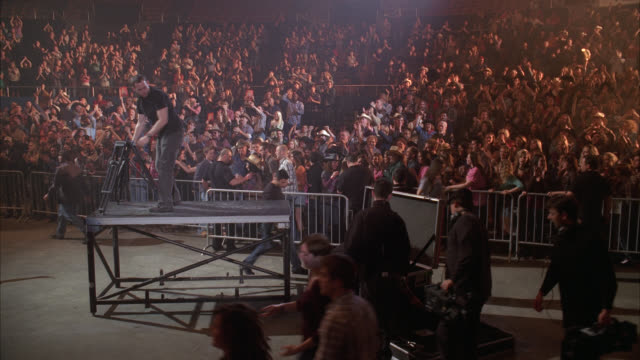 wide angle of crowds, spectators, or audience at concert or convention center. crew visible setting up equipment in fg. barricades visible. - concert hall stock videos & royalty-free footage