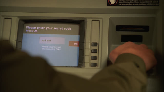 medium angle of atm machine. man partially visible next to atm. digital display or monitor. man enters code onto keypad. - bank stock-videos und b-roll-filmmaterial