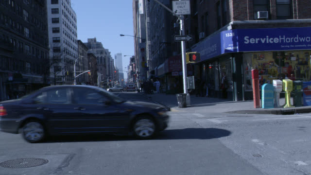 pan up of nyc street. cars driving, store, one way street sign, buildings. - one way stock videos and b-roll footage