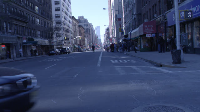 pan up of nyc street. cars driving, store, one way street sign, buildings. - one way stock videos & royalty-free footage