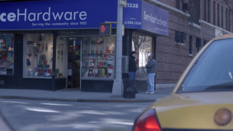 wide angle of nyc street. pov from inside car stopped behind taxi in traffic. one way street sign, buildings. hardware store on corner. pedestrians. gridlock. - one way stock videos & royalty-free footage